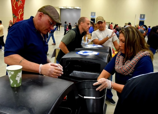 Chief Master Sgt. Tony Rittwager, 433rd Maintenance Operations Squadron superintendent, and his wife Diane, sort through recyclable plastic and aluminum during H-E-B's 26th Annual Feast of Sharing Dec. 23, 2018, at the Henry B. Gonzalez Convention Center in San Antonio, Texas. Spouses, children, friends and family served food and drinks, cleaned tables, sorted recyclables and provided fellowship to the assembled guests, who came from throughout the Military City U.S.A area to share the dinner.