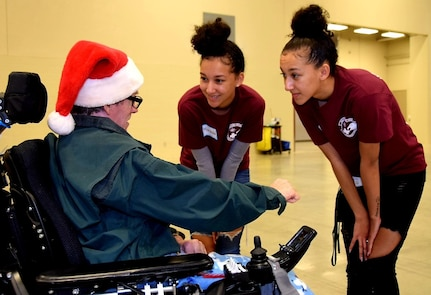 Identical twins, Airmen 1st Class Maranda Smith, 433rd Aerospace Medicine Squadron health services technician and Mariah Smith, 433rd Force Support Squadron communications technician, talk with a guest at H-E-B's 26th Annual Feast of Sharing Dec. 23, 2018, at the Henry B. Gonzalez Convention Center in San Antonio, Texas. This was the Smith sisters first time serving at the event that served over 10,000 meals to area resident from the Alamo City area.