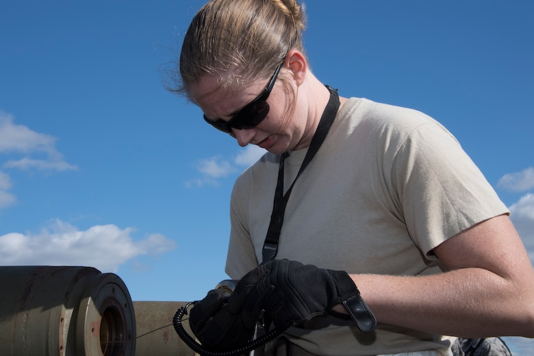 U.S. Air Force Staff Sgt. Ashley Johnson, a munitions technician assigned to the 707th Maintenance Squadron, performs maintenance on a munition during Ample Strike 18 at Royal Air Force Fairford, England, Sept. 7, 2018.   When not building munitions, Johnson can be found practicing her love of art. (U.S. Air Force photo by Master Sgt. Ted Daigle)