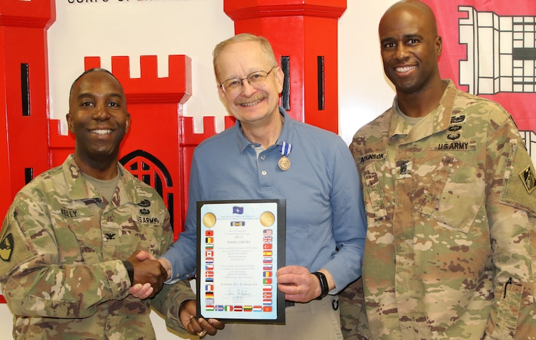 Mark A. Coburn is beaming with pride as he is presented the NATO medal from Afghanistan District Commander, Col. Jason E. Kelly and Command Sergeant Major Nathaniel Atkinson.