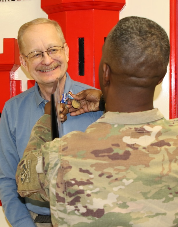 Col. Jason E. Kelly, Afghanistan District Commanding Officer pins the Global War on Terrorism Medal and NATO medal on Mark A. Coburn for his outstanding work ethics while deployed in support of Operation Freedom's Sentinel.