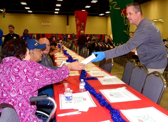 Lt. Col. Marc Mulkey, 733rd Training Squadron commander, passes out boxes of cookies to one of the 10,000 guests at  H-E-B's 26th Annual Feast of Sharing Dec. 23, 2018, at the Henry B. Gonzalez Convention Center in San Antonio. Mulkey brought his wife and children to help serve at the event and he said that he hopes to bring his family to serve again next year.