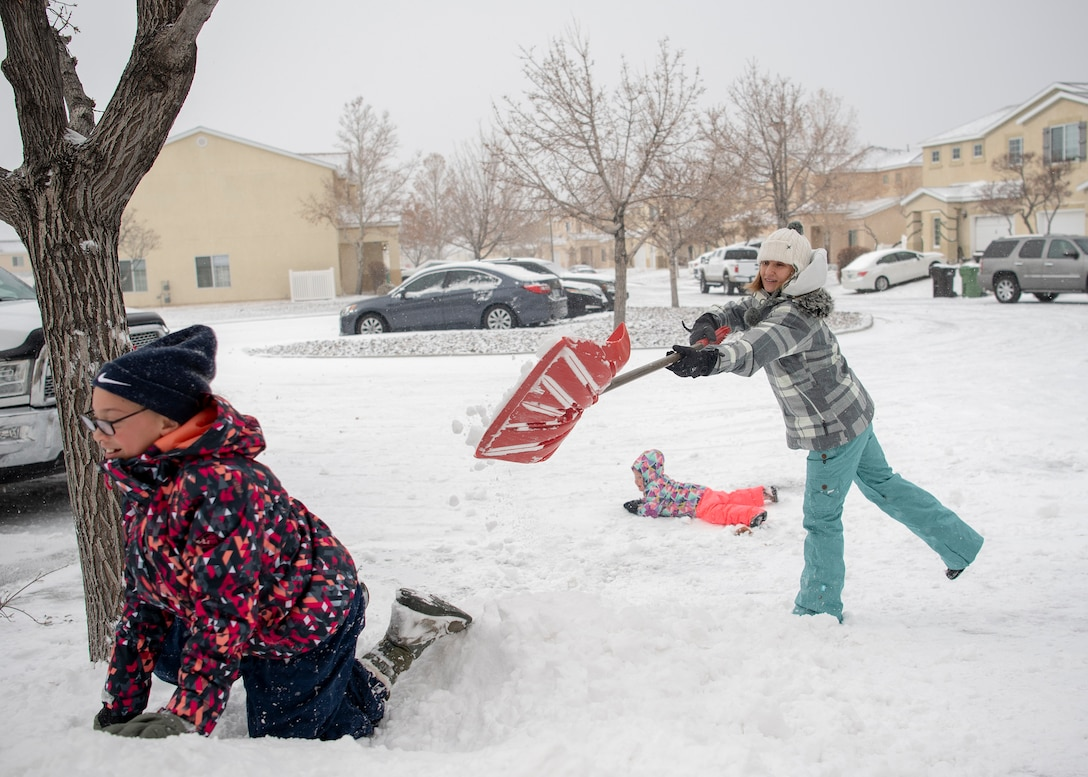 Tech. Sgt Kimberly Strong, Space Rapid Capabilities Office directors action group noncommissioned officer in charge, plays with her daughters Peyton 10, left and Cadence Strong 3, after a snowstorm that blanketed the Albuquerque area and prompted closure of Kirtland Air Force Base to non-mission essential personnel on Dec. 27, 2018.