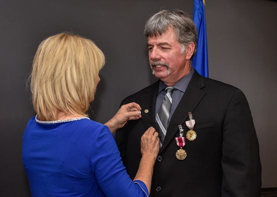 Joseph Nevins, 58th Maintenance Group deputy director, is given his retirement pin by his wife Lisa at Kirtland Air Force Base, N.M., Jan. 4, 2019. Nevins served his country both as an Airman and as a civil servant with nearly 43 years of service. Nevins has served as the 58th Maintenance Group deputy director here from 2004-2019, where he directed and integrated the efforts of 936 personnel supporting the execution of a 12,000 hour annual flying program for the Air Education and Training Command formal aircrew training schools for special forces and air rescue personnel. (U.S. Air Force photo by Airman 1st Class Austin J. Prisbrey)