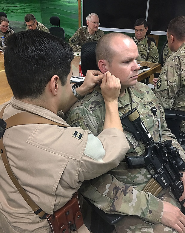 Air Force Capt. Christopher Sandoval places a needle in the outer ear of Army Sgt. 1st Class David Ussery during a four-hour Battlefield Acupuncture class given Nov.18 at Craig Joint Theater Hospital certifying an additional 12 providers.