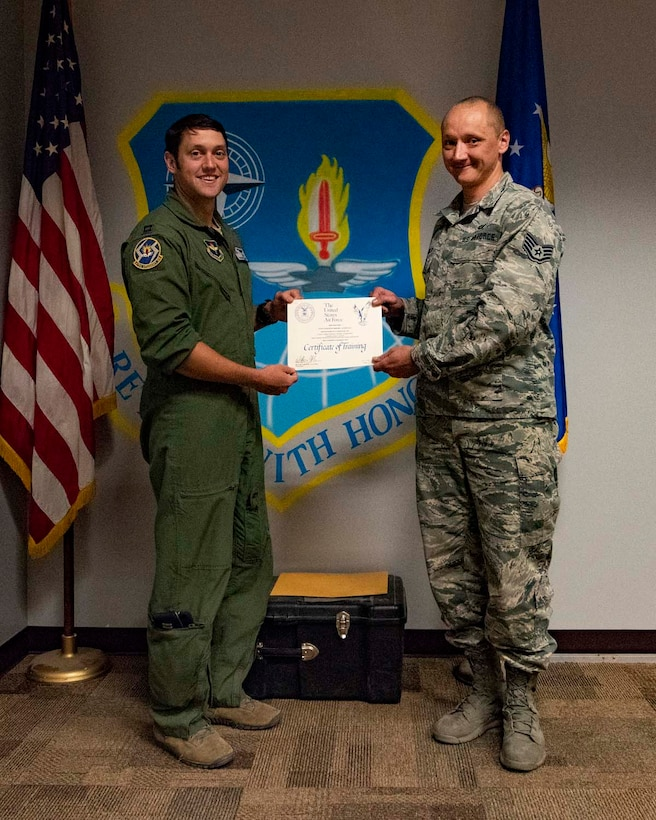 Staff Sgt. Mikhail Scheglov, a finance technician with the 141st Comptroller Flight, poses with Capt. Ryan Adams, a pilot with the 58th Training Squadron, during their graduation ceremony upon completing the Survival, Evasion, Resistance and Escape SV-80A combat survival training course. Scheglov completed several SERE training courses in preparation for a trip to Vinnytsia Air Base, Ukraine, in which he served as a translator during exercise Clear Sky 2018.  (U.S. Air National Guard photo by Staff Sgt. Rose M. Lust)