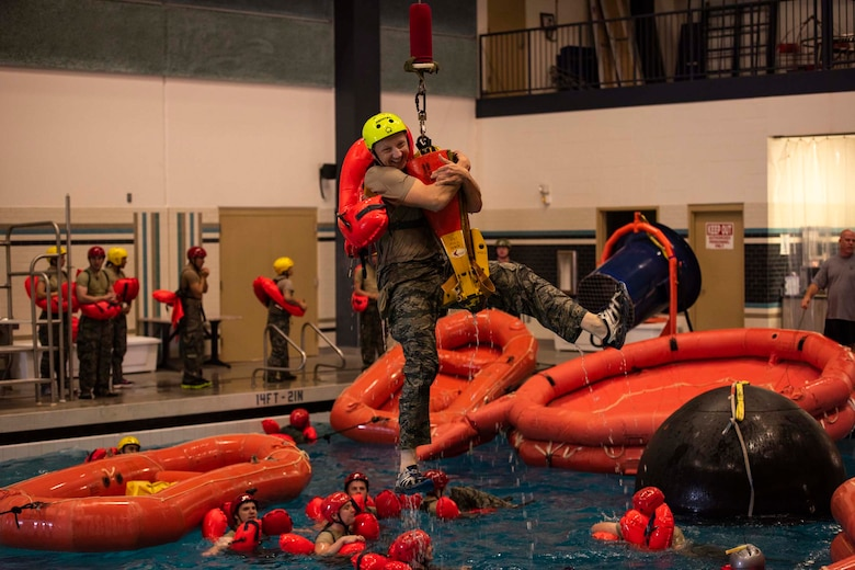 Staff Sgt. Mikhail Scheglov, a finance technician with the 141st Comptroller Flight, smiles as he's hoisted out of the pool during SV-90A parachute water survival training Aug. 2, 2018 at Fairchild Air Force Base, Wash. Scheglov completed several Survival, Evasion, Resistance and Escape training courses in preparation for a trip to Vinnytsia Air Base, Ukraine, in which he served as a translator during exercise Clear Sky 2018. (U.S. Air National Guard photo by Staff Sgt. Rose M. Lust)