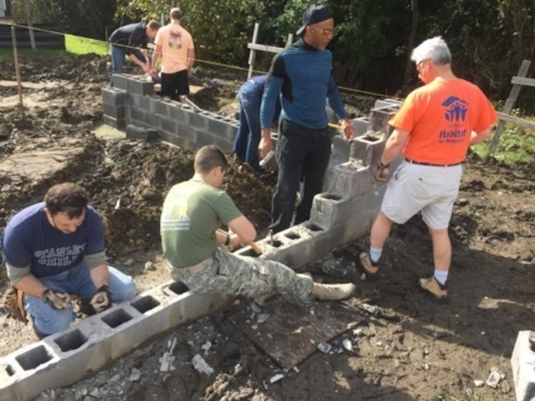 Space and Naval Warfare Systems Center (SSC) Atlantic New Professionals (NPs) help lay the foundation for a new Habitat for Humanity home.