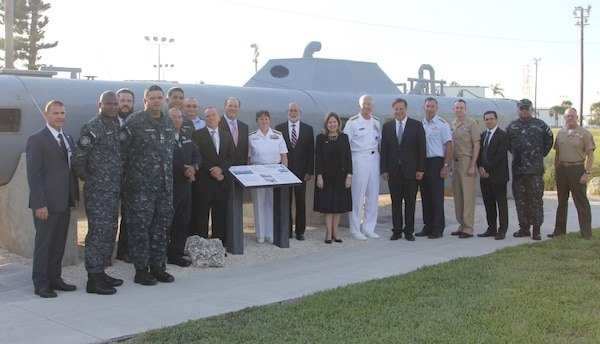 Panamanian President Juan Carlos Varela and U.S. and international leaders in front of a static display of a self-propelled semi-submersible (SPSS), located outside JIATF South.
