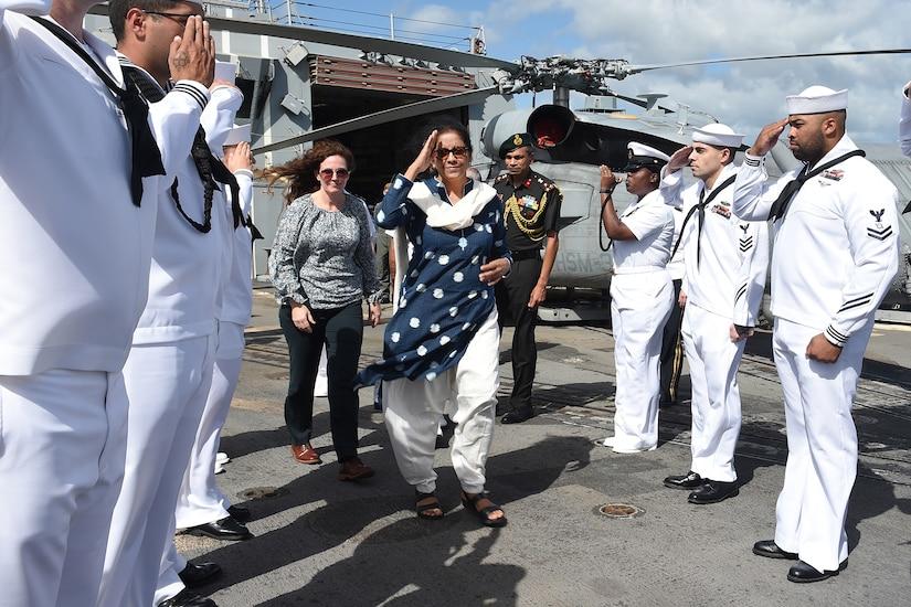 Sailors salute a dignitary.