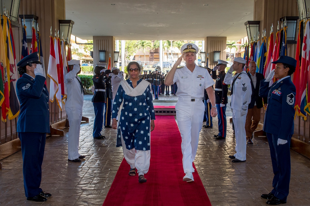 Service members salute a dignitary.