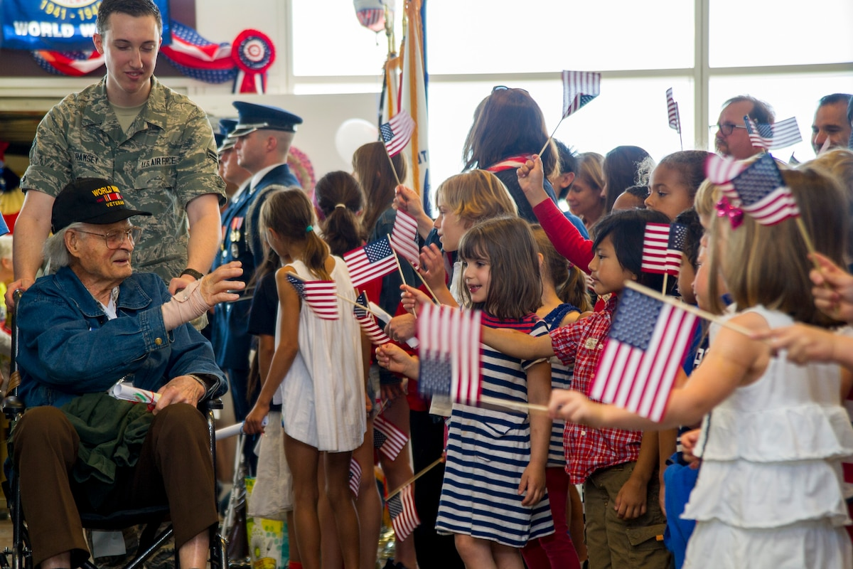A group of children holding miniature American flags greet a veteran in a wheelchair being pushed by an airman.