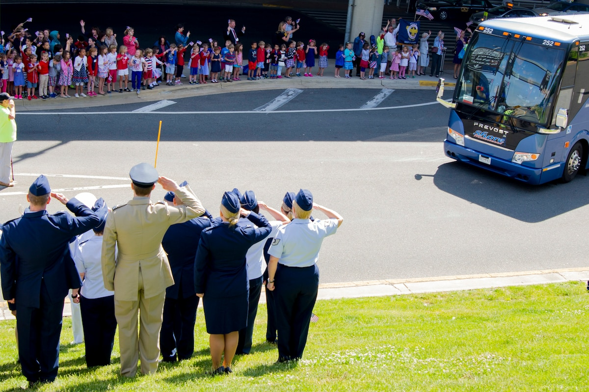 A group of people stand along  both sides of a road saluting and waving at a bus driving by.
