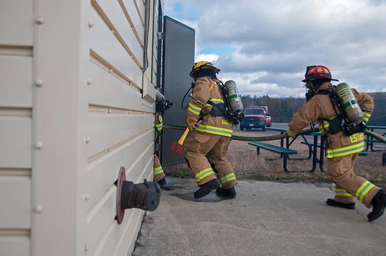 Airman 1st Class Shawn Burgmyer, 104th Civil Engineering Squadron firefighter, and Lt. Dan Estee, 104th CES shift officer, particpiate in live structural fire training Nov. 27, 2018, at Barnes Air National Guard Base, Massachusetts. The training ensures the Fire Attack Teams are prepared to respond to any fires on base or in the surrounding communities. (U.S. Air National Guard photo by Airman 1st Class Randy Burlingame)
