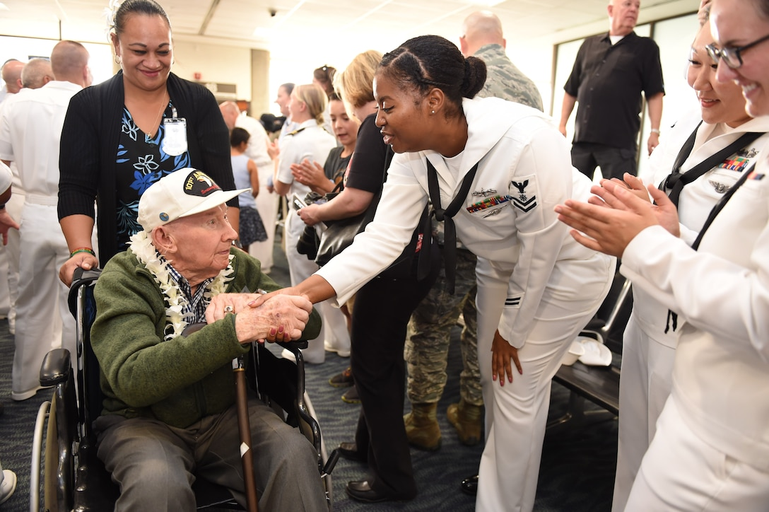 A man being pushed in a wheelchair by a woman shakes hands with sailors lined up in an airport terminal.