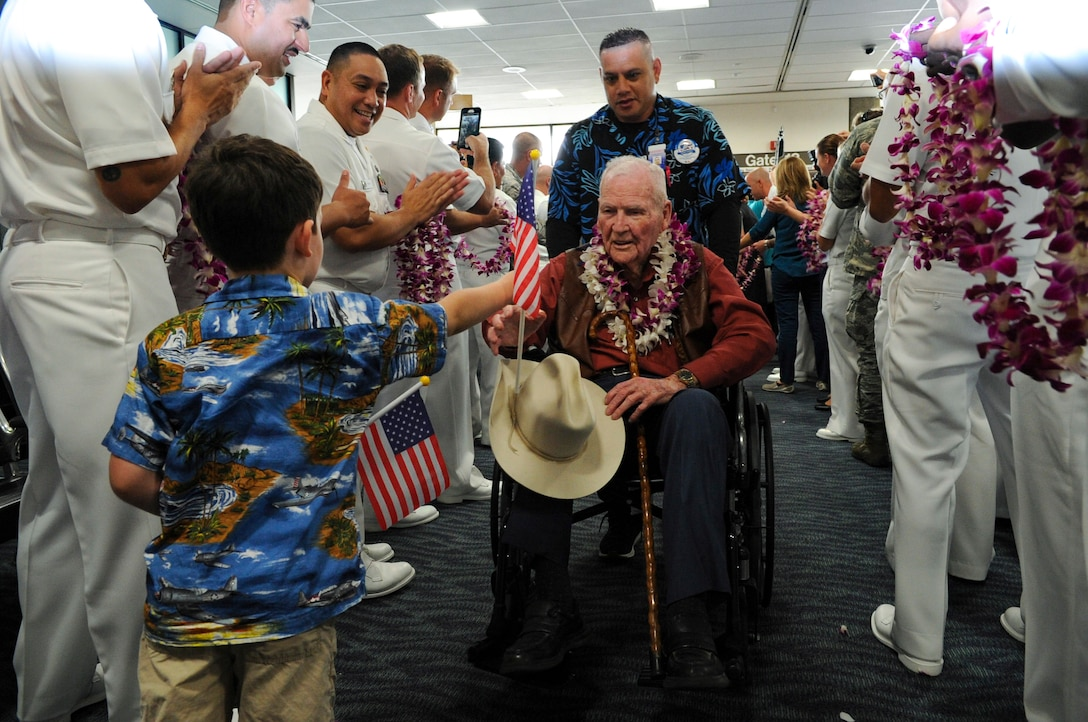 A child hands a man in a wheelchair an American flag as the man is being pushed in-between two rows of people.