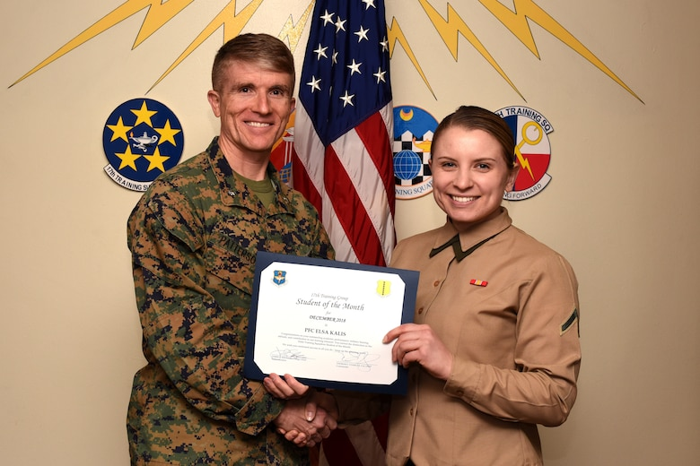 U.S. Marine Corps. Lt. Col. Earl Patterson, Marine Corps. Detachment at Goodfellow commanding officer, presents the 316th Training Squadron Student of the Month award to Pfc. Elsa Kalis, 316th TRS student, at the Brandenburg Hall on Goodfellow Air Force Base, Texas, Jan. 4, 2019. The 316th TRS's mission is to conduct U.S. Air Force, U.S. Army, U.S. Marine Corps, U.S. Navy and U.S. Coast Guard cryptologic, human intelligence and military training. (U.S. Air Force photo by Airman 1st Class Zachary Chapman/Released)