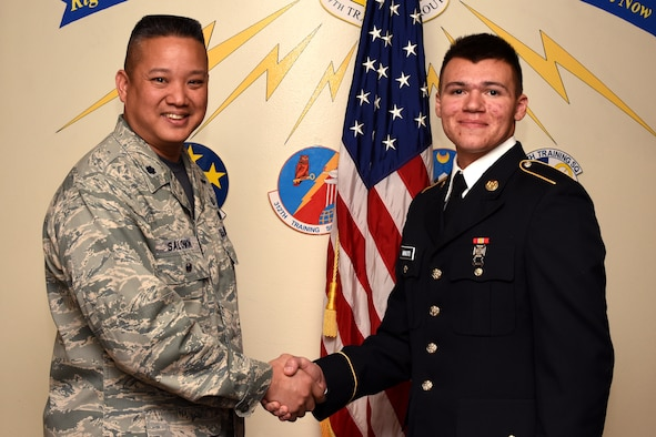 U.S. Air Force Col. Abraham Salomon, 17th Training Group deputy commander, congratulates the 312th Training Squadron Student of the Month winner, U.S. Army Pvt. Christopher Minotti, 312th TRS student, at the Brandenburg Hall on Goodfellow Air Force Base, Texas, Jan. 4, 2019. The 312th TRS's mission is to provide Department of Defense and international customers with mission ready fire protection and special instruments graduates and provide mission support for the Air Force Technical Applications Center. (U.S. Air Force photo by Airman 1st Class Zachary Chapman/Released)