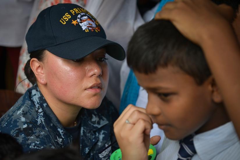 A service member paints a student's face.