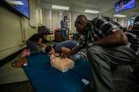 Terri Watkins (right), the director of Marine Corps Base Hawaii (MCBH) Base Safety, helps a Mokapu Elementary School staff member during a First Aid training class, MCBH, Jan. 4, 2019. The class provided cardiopulmonary resuscitation, first aid, and automated external defibrillator training to the school staff to ensure the safety and well-being of all students at Mokapu Elementary School. (U.S. Marine Corps photo by Cpl. Matthew Kirk)