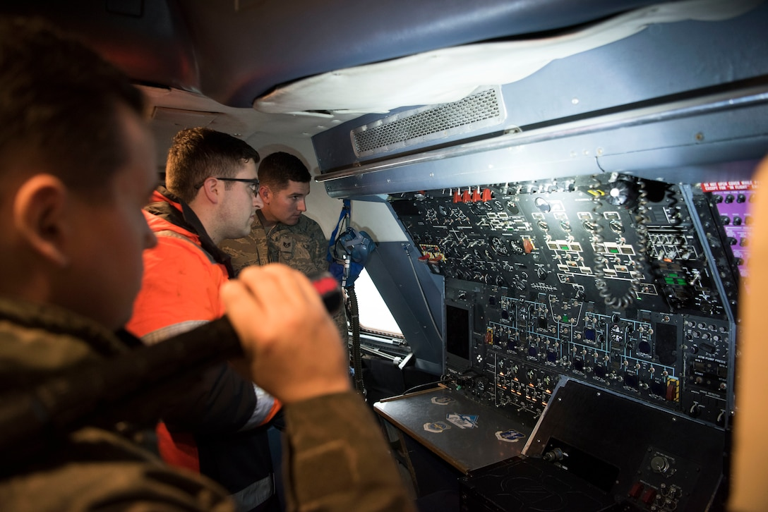 U.S. Air Force Staff Sgt. Ryan Johnson, 521st Air Mobility Operations Wing regional training center crew chief, illuminates part of the cockpit in the C-5M Super Galaxy aircraft while he quizzes Airmen on running auxiliary power units Dec. 3, 2018, on Ramstein Air Base, Germany. The Airmen in this course belonged to the 725th Aircraft Maintenance Squadron from Naval Station Rota, Spain and the 726th AMS from Spangdahlem Air Base, Germany. (U.S. Air Force photo by Airman 1st Class Kristof J. Rixmann)