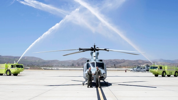 Two Marine pilots shake hands in front of the last UH-1y Venom delivery while two flight-line firetrucks spray their water cannons in the air.