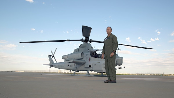 Marine pilot stands in front of a AH-1Z Viper on a flight line.