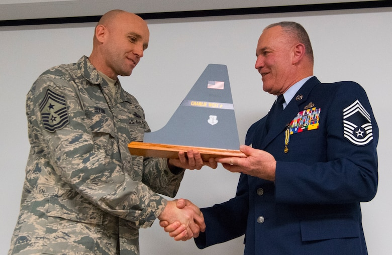 Chief Master Sgt. Jame Dixon, West Virginia Air National Guard State Command Chief, presents a tail flash to Chief Master Sgt. Fred Turner during a formal retirement ceremony held Jan. 4, 2019, at McLaughlin Air National Guard Base, Charleston, W.Va. Turner served in the California and West Virginia Air National Guard for 41 years cumulatively and was also the 12th State Command Chief for the West Virginia Air National Guard. (U.S. Air National Guard photo by Master Sgt. De-Juan Haley)