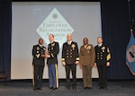 DLA director Army Lt. Gen. Darrell Williams, left, presents United States Army Maj. Grant Thimsen, DLA Distribution San Joaquin, California, operations officer, with the DLA Field Grade Officer of the Year award at the 51st annual employee recognition ceremony Dec. 13. Distribution commanding officer Navy Supply Corps Rear Adm. Kevin Jones, third from right, DLA Distribution San Joaquin commander Marine Col. Andre Harrell, second from right, and DLA senior enlisted leader Navy Command Master Chief Shaun Brahmsteadt, far right, were also on-hand to present the award.  (Photo by Teodora Mocanu)