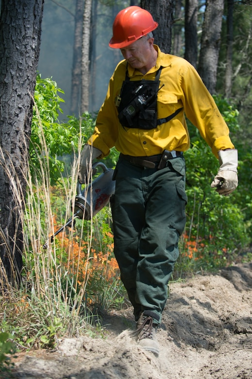 Terrence Larimer, natural resources manager assigned to the 628th Civil Engineering Squadron, uses a hand-held torch during a prescribed fire operation at the Joint Base Charleston Naval Weapons Station, May 6, 2014.