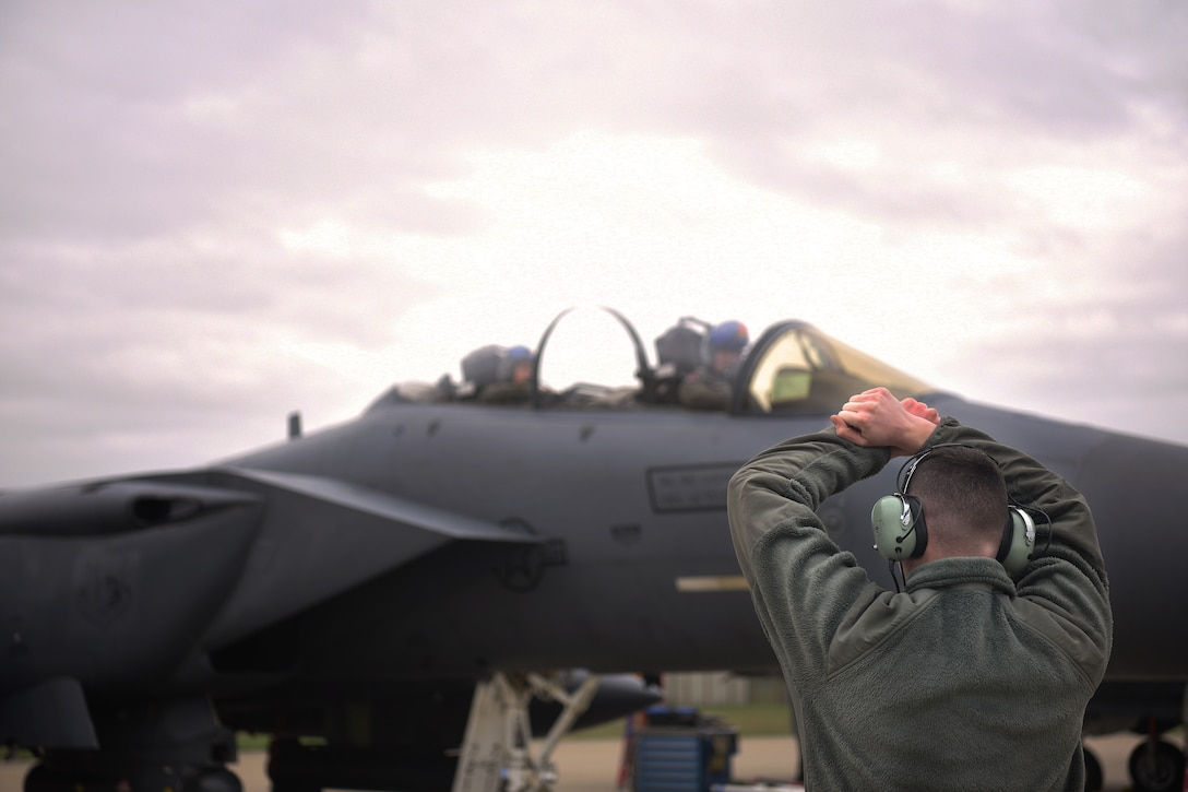 A 492nd Aircraft Maintenance Unit crew chief marshals an F-15E Strike Eagle at Royal Air Force Lakenheath, England, Jan. 7, 2019. Aircraft marshalling is a method of visual communication between aircrew and crew chiefs as an alternative to radio communication. (U.S. Air Force photo by Airman 1st Class Shanice Williams-Jones)
