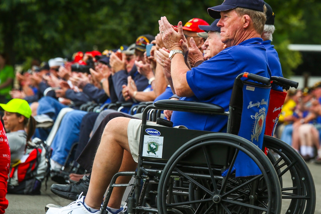 A group or veterans sitting in wheelchairs clap.