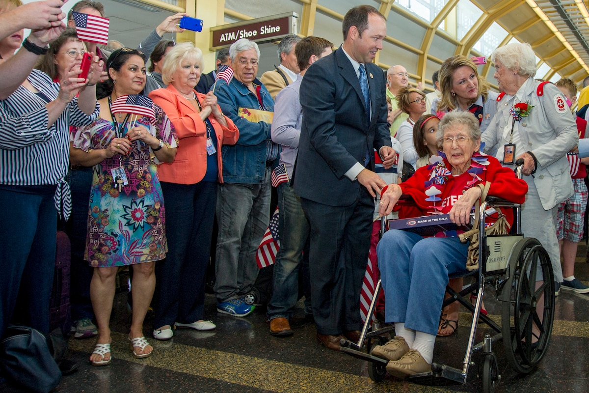 People wave small American flags as a veteran in a wheelchair proceeds past hem in an airport hall.