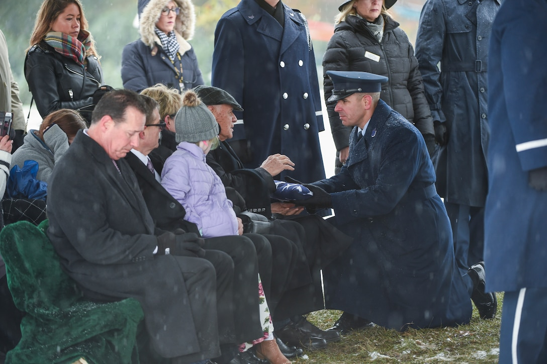 DIA Command Senior Enlisted Leader Chief Master Sgt. Benjamin Higginbotham presents the burial flag to Frank Henrion, husband of the late Chief Master Sgt. Therese Henrion, during her graveside burial at Arlington National Cemetery, Nov. 15, 2018.