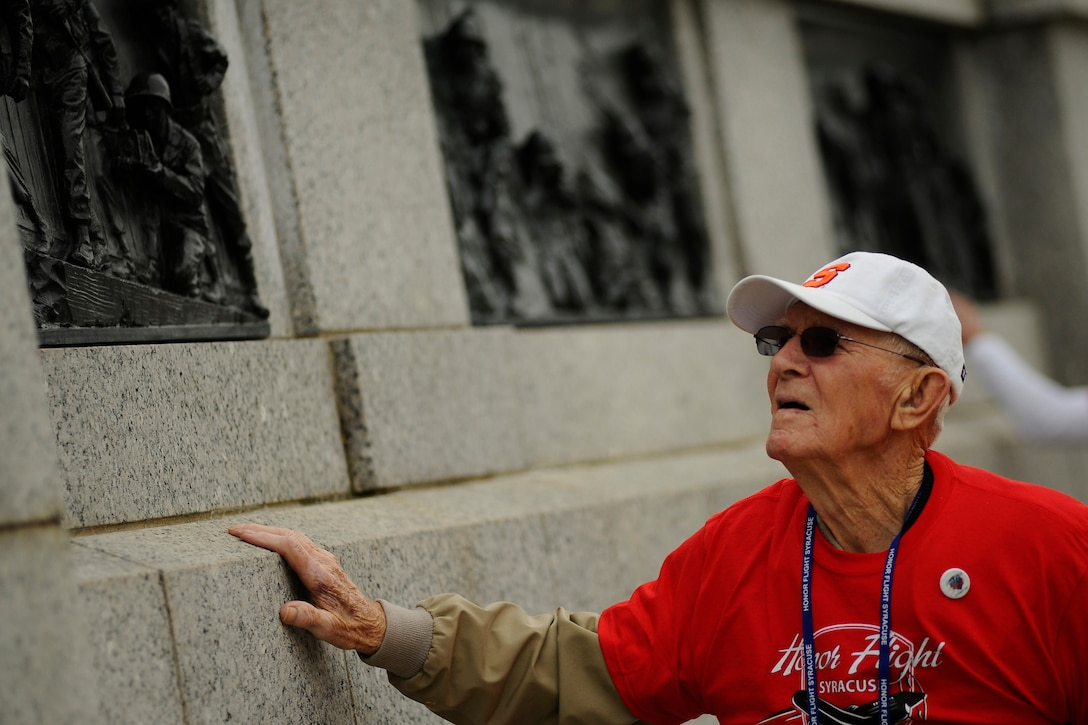 A man looks up at artwork on a memorial wall.
