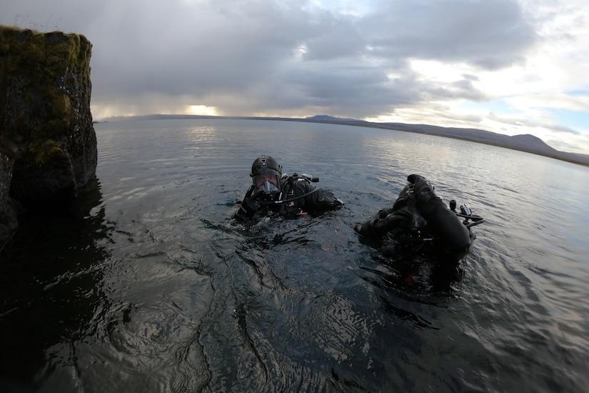 Sailors in scuba gear prepare to depart the ocean.