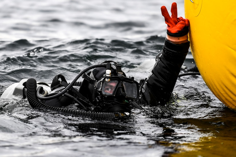 Sailor in dive gear hand signals while in the ocean.