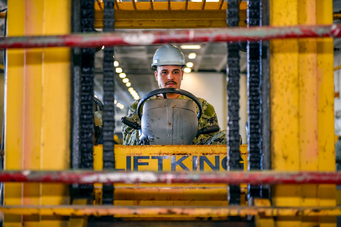 A sailor operates a forklift on a navy ship.