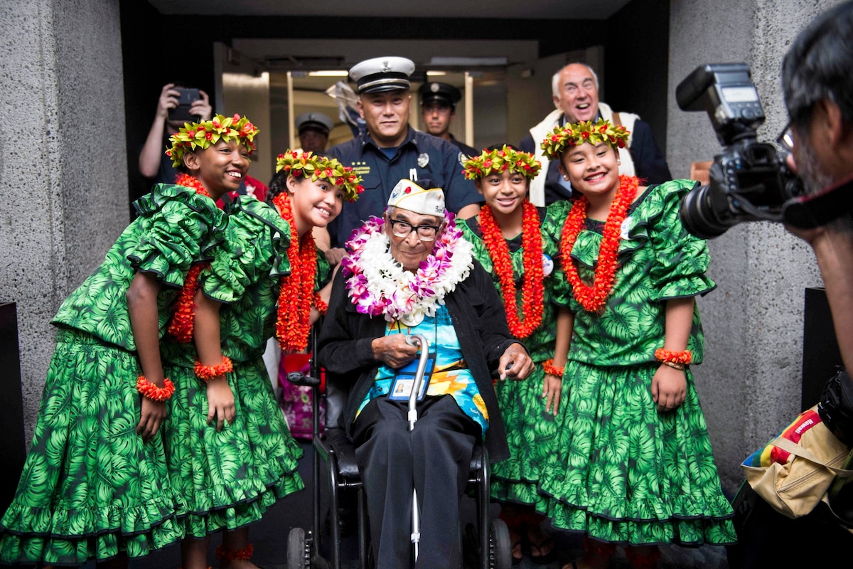 A veteran in a wheelchair flanked by smiling hula dancers smiles for a photo.