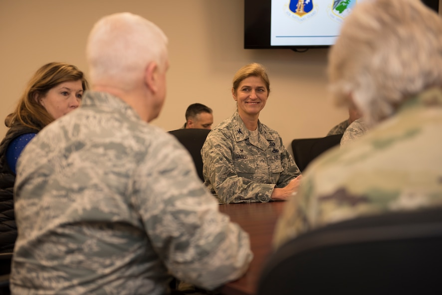 Lt. Gen. L. Scott Rice, director of the Air National Guard sits at a board table with 102nd Intelligence Wing leadership.
