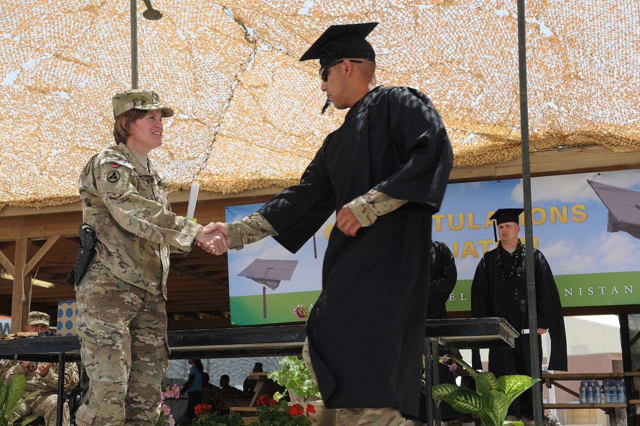 A man in a cap and gown shakes hands with an Army general on a graduation stage.