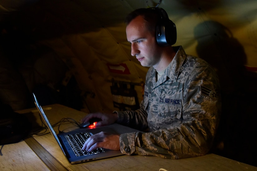 An airman clicks a mouse while looking at a laptop.
