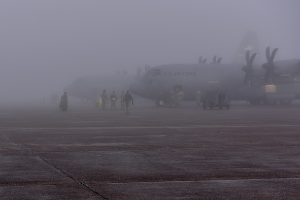 People walk in foggy area beside C-130Js on right of screen.