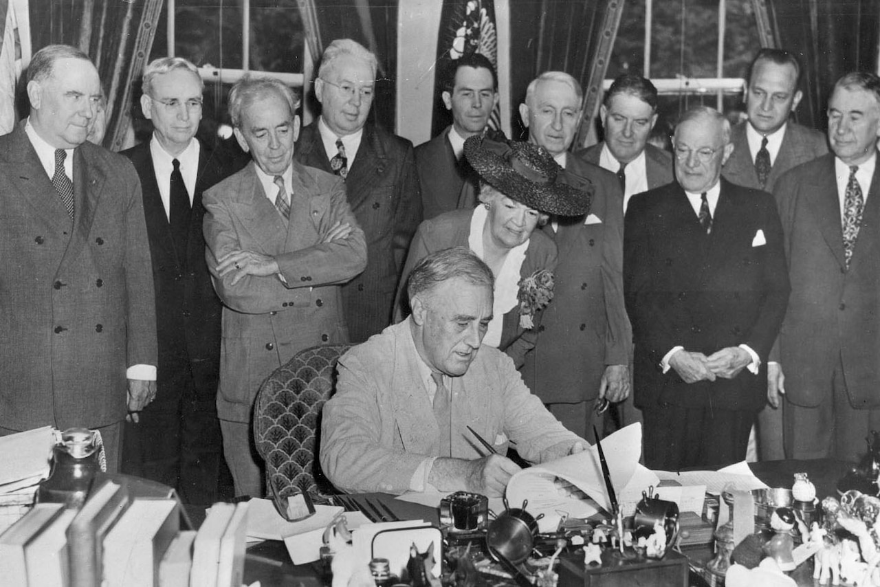 President Franklin D. Roosevelt signs the GI Bill at a table surrounded by people.