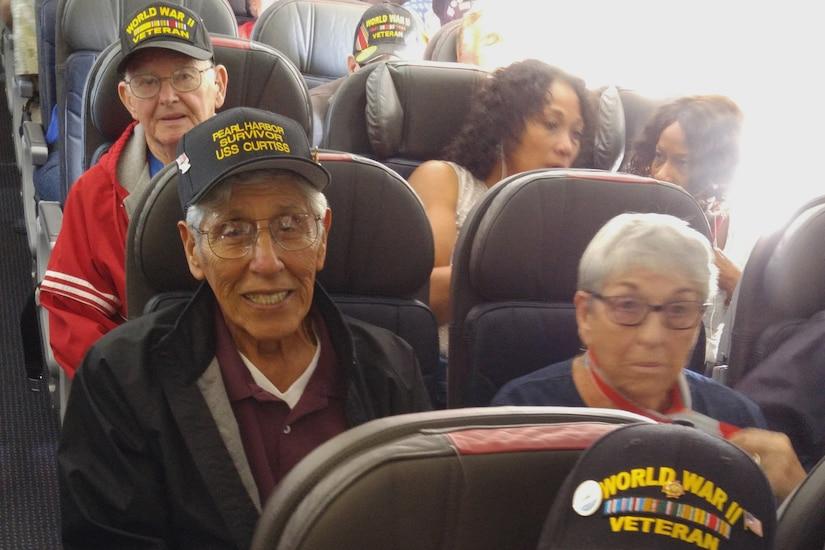 World War II veterans relax on a plane to Hawaii.