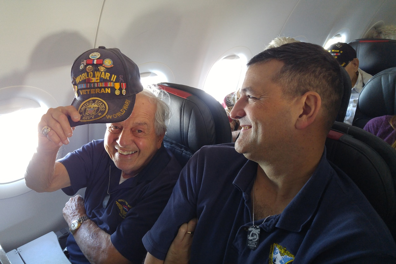 A World War II veteran tips his cap toward the camera while in an airplane window seat.