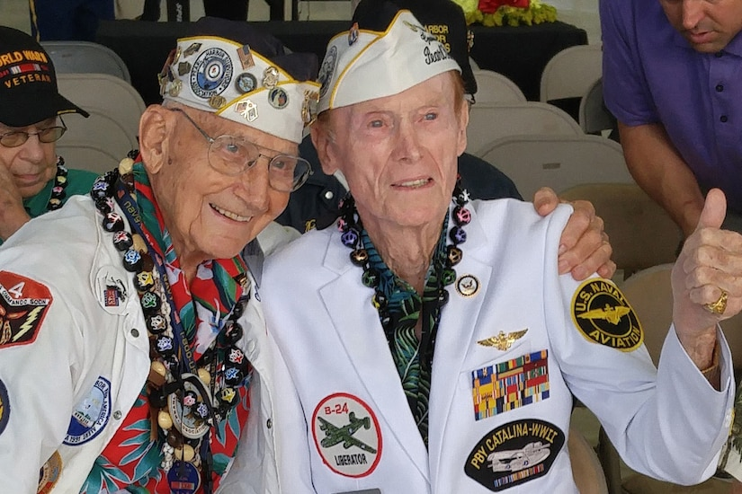 Two Pearl Harbor survivors hug and give a thumbs-up to the camera.