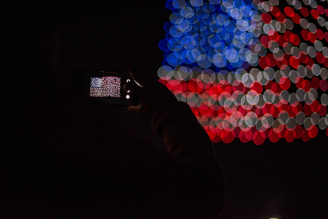 An audience member takes a photo during the Intel Shooting Star Drone light show at Travis Air Force Base, Calif., July 5, 2018. The drones conducted a show consisting of various designs meant to highlight both the U.S. Air Force's and Travis' history. (U.S. Air Force photo by Master Sgt. Joey Swafford)