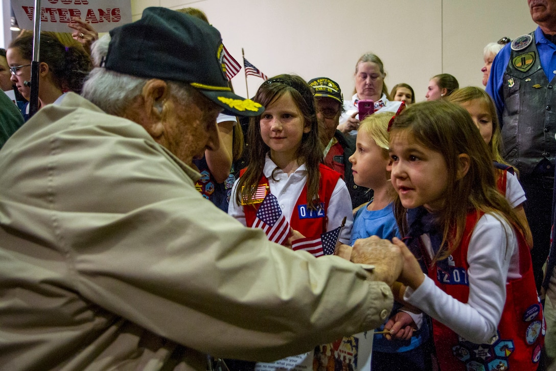 A group of young girls greet an old man.