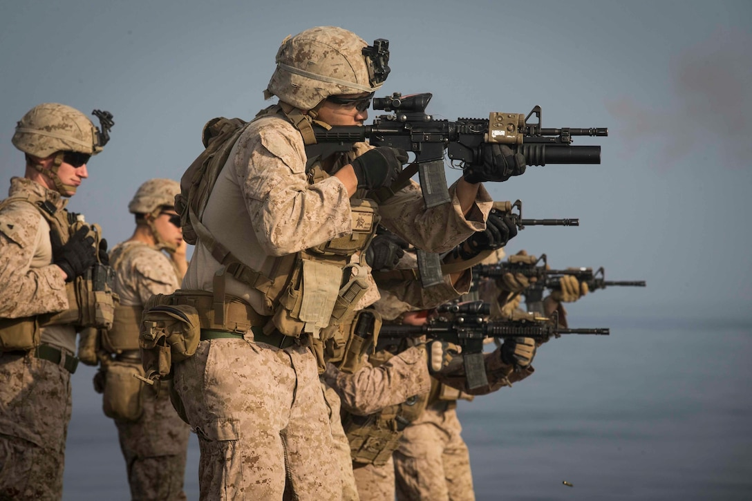 Marine Corps fire weapons aboard a ship.